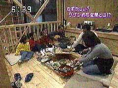 火が入った囲炉裏を囲んで平野さんご家族と設計者佐山がなごむ